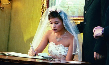 A woman in a wedding dress signs the wedding register