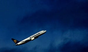 A Ryanair aircraft flying into a darkened sky