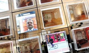 A man looking in an estate agent window