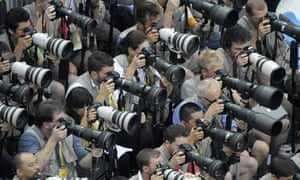A bank of press photographers
