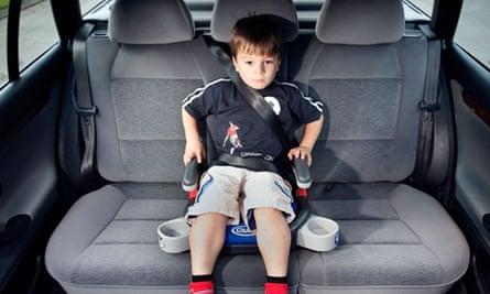 A boy in a car booster seat