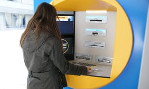 A woman uses a contactless ATM in Spain