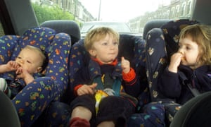 Three children of different ages in forward-facing child car seats