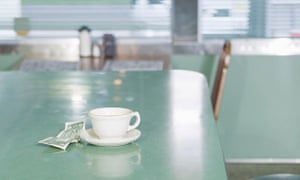 Coffee cup and money on diner counter