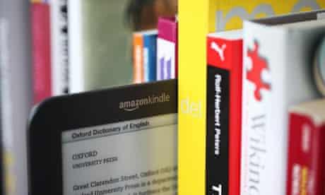 A Kindle alongside some paper books