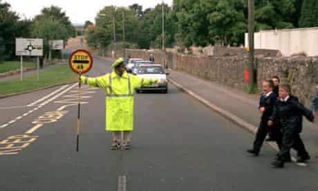 A school crossing (lollipop lady) helping children cross a road