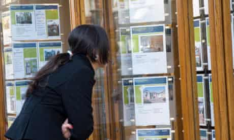 A young woman looking in an estate agent window