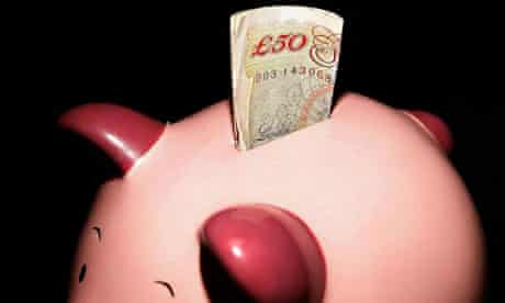 Piggy bank with roll of banknotes sticking out of the top