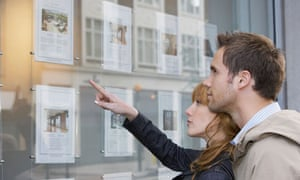 A couple looking in an estate agent's window