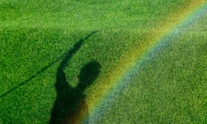 A rainbow forms over the shadow of a garden at Hampton Court Palace Flower Show, London