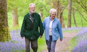 An elederly couple walking in a wood