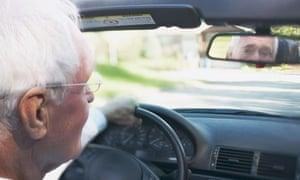 An older man driving a car
