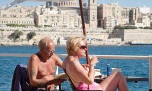 Older british couple sunbathing in Valletta, Malta