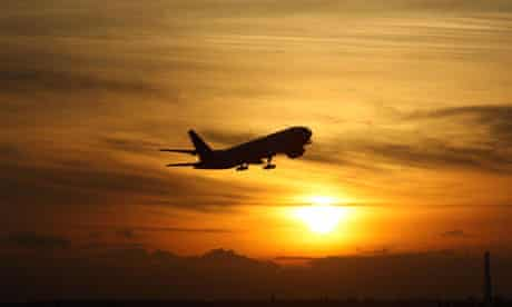 A plane takes off from Heathrow airport, UK, against a sunset background