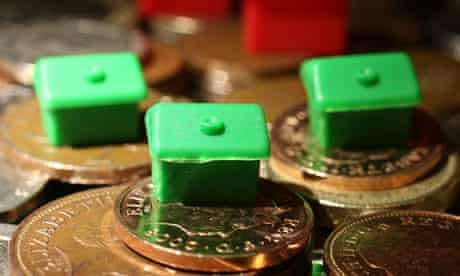 Monopoly houses on a pile of coins