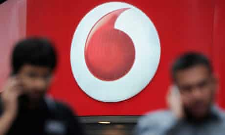 A Vodafone sign flanked by people using mobiles