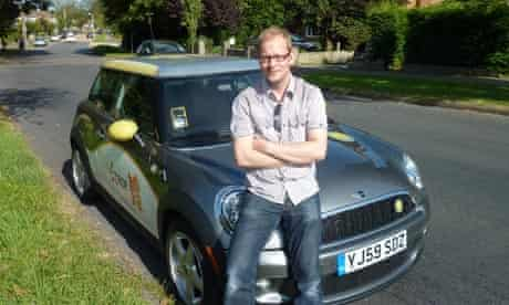 Mark King relaxes on the bonnet of a BMW Mini E
