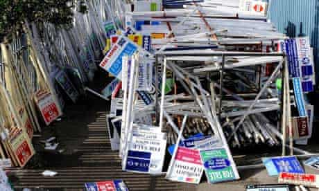 Estate agent signs piled up in a yard