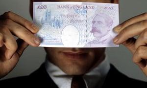 A man hiding behind a £20 note