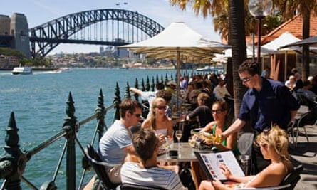 Young people relaxing in warm sunshine at a cafe on Circular Quay, Sydney, Australia