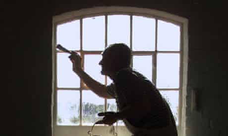 A decorator painting a window