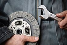 Car Mechanic with spanner and clutch plate