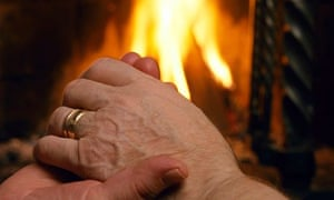 An old couple sitting hand in hand by the fireplace