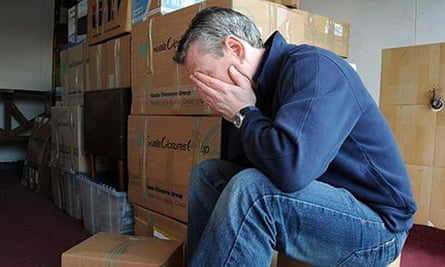 Man with head in hands and pile of removal boxes