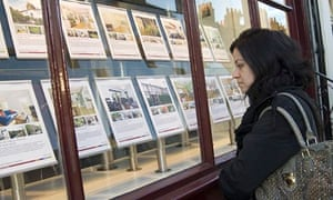 Young woman looking at the property for sale in estate agents window