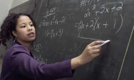 A Maths teacher writing on a blackboard