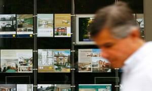 A pedestrian passes a branch of an estate agent