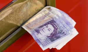 UK £20 bank notes sticking out of a red front door letterbox