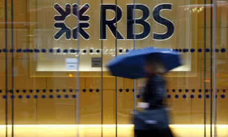Woman with an umbrella walks in front of office with RBS logo