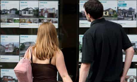 A young couple look in an estate agent window