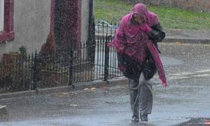 A woman walking through heavy rain