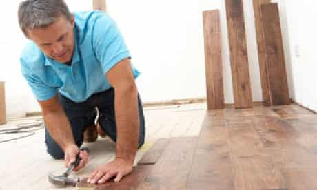 A builder or carpenter laying a wooden floor