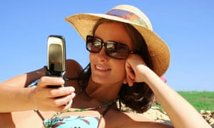 A woman using a mobile phone on the beach