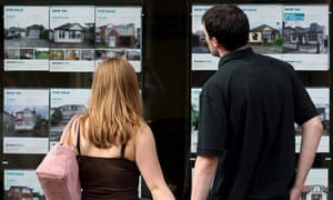 Young couple looking in an estate agent's window