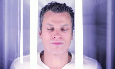 Young man, eyes closed, in cryogenics chamber