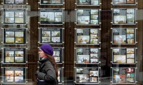 A woman walks past an estate agent window