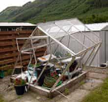 Green house lies destroyed after wind damage in a garden