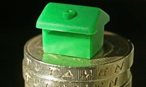A Monopoly house sitting on some pound coins