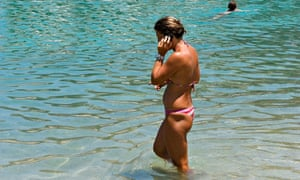 Woman on a mobile phone in the sea