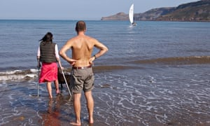 Couple paddling in the sea , women on crutches. Runswick Bay North Yorkshire England.