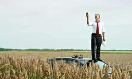 man on top of car in field