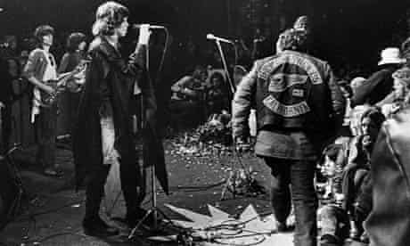 Mick Jagger sings at the Altamont rock festival at Livermore, California, Dec 6, 1969 while Hells Angels cross stage during melee to help fellow motorcyclists