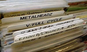 Man searches through racks of vinyl at a record shop