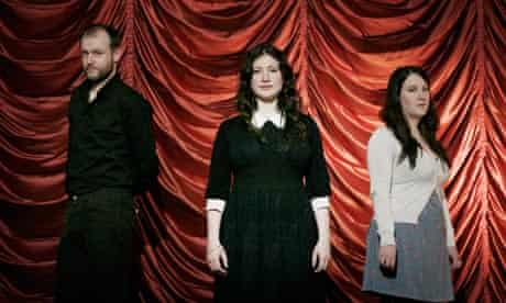 Adrian McNally with Rachel and Becky Unthank in front of red satin drapes