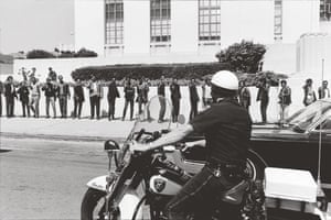 Howard Bingham photos: A row of Black Panthers pretend to shoot at a motorcycle cop