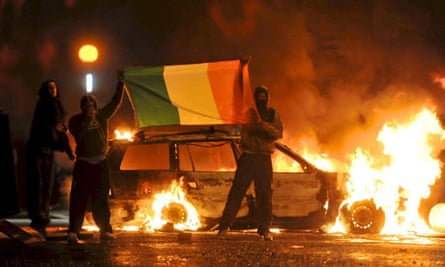 Men hold the Irish flag in front of burn